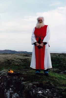 An elderly man wearing red and white robes standing in an open area.