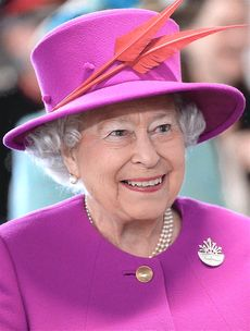 A smiling woman wearing a purple dress and matching hat.