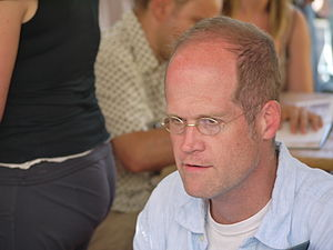 A color photograph of a seated, middle-aged man with a receding hairline. He is wearing spectacles, a white undershirt and a light blue collared shirt. He looks left past the camera.