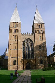 A simple Norman west front with two towers surmounted by short pyramidal spires. A large Gothic window has been inserted between the towers.