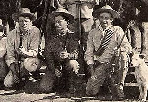 Photo taken in 1893 of three Bulawayo field scouts kneeling in front of their horses. Bob Bain on the left, Burnham in the middle, Maurice Gifford and his dog on the right.  Burnham is dressed in his Arizona clothes and is holding his Winchester model 1873 .44WCF rifle