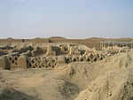 Ruins of former buildings in a desert setting consisting of low walls with a fishnet pattern.