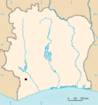 A blank map of a square-shaped country with a black dot designating the location of the site.