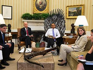 President Obama sits on the Iron Throne in the Oval Office of the White House, surrounded by other people