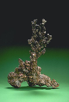 An irregular piece of native copper on a green background.