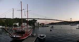 A docked sailboat floats in front of a suspension bridge, at twilight.