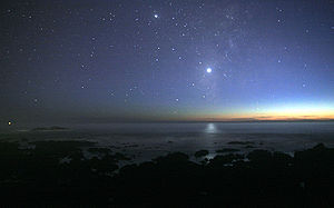 A photograph of the night sky taken from the seashore. A glimmer of sunlight is on the horizon. There are many stars visible. Venus is at the center, much brighter than any of the stars, and its light can be seen reflected in the ocean.