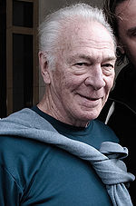 Upper torso of a gray-haired old man. He is wearing a teal T-shirt with a grey sweater tied around his neck.