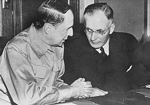 Two men seated at a table side by side talking. One is wearing a suit, the other a military uniform.