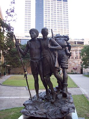 A bronze statue depicting a Papuan man assisting a wounded soldier down a muddy track while another soldier advances in the other direction