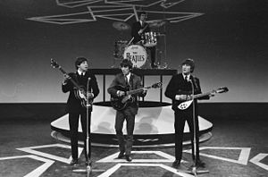 Monochrome image of The Beatles performing on a stage wearing dark suits