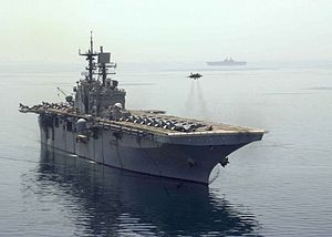 A jet aircraft hovering above flight deck of a large military ship, with several aircraft visible on the deck.