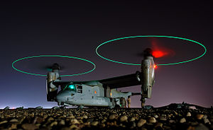 Ground crew refuel an MV-22 before a mission in central Iraq at night. The rotors are turning and the tips are green, forming green circles.