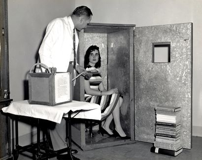 photograph of a woman, sitting on a chair which is in a large, wardrobe-sized  box, the open door of which has a small window. A man stands nearby, holding a breathing apparatus.