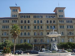 "A view of one of Viareggio's grand hotels along the passeggiata, with the ""Fountain of the Four Seasons"" by Beppe Domenici in front."