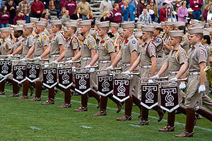Row of students in uniform with knee-high boots.  Each holds a bugle that dangles a pennant.