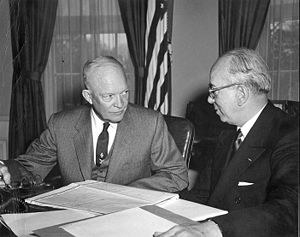 Two men in suits at a table covered in papers. There is an American flag in the background.