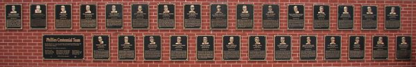 Forty black metal plaques are mounted on a brick wall. They are inscribed with gold images of human faces and text.