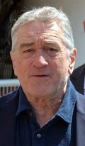 Photo of Robert De Niro—a white man of 70 years with white hair, wide nose, square face and small eyes, wearing a dark blue shirt—at the 2016 Cannes Film Festival.
