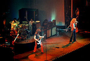 A colour photograph of the four members of Led Zeppelin performing onstage, with some other figures visible in the background.
