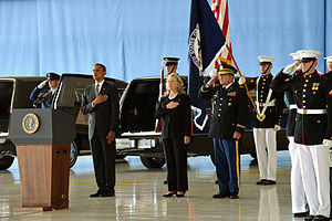 Obama and Clinton at a somber occasion, honoring the Benghazi attack victims at the Transfer of Remains Ceremony, held at Andrews Air Force Base on September 14, 2012. There are soldiers standing behind Obama and Clinton, and everyone is standing on a large wooden floor with their left hands to their side and their right hands on their upper chests.