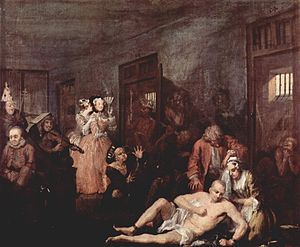 "An 1735 oil version of the last scene from William Hogarth's A Rake's Progress, the story of a rich merchant's son, Tom Rakewell whose immoral living causes him to end up in Bethlem. A shaven-head and near-naked Rakewell is depicted in one of galleries of Bethlem. He sits on the floor while his right leg is being manacled by an attendant. A wigged doctor is standing over him.  Rakewell's spurned fiancé kneels beside him, crying. Inmates exhibiting various stereotypical forms of madness are shown in their open cells and in the corridor. Two fashionably dressed lady-visitors standing by the cell of a ""urinating mad monarch"", are clearly amused by the show. One holds a fan up to her face and is clearly smiling while her companion whispers in ear. Hogarth became a governor of Bethlem in 1752."