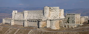 A stone castle with two high curtain walls, one within the other. They are crenelated and studded with projecting towers, both rectangular and rounded. The castle is on a promontory high above the surrounding landscape
