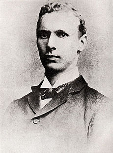 A young man in a dark jacket with a dark bow tie
