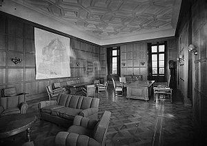 A black and white image of a large room, with two large windows on the back wall, with two more walls coming away from this wall at right angles. There are a number of large sofas spaced around the room, as well as single chairs, and a large desk surrounded by chairs. On the walls that do not have windows, one has a large map of northern Europe, whilst the other wall has a large doorway leading out of the room.