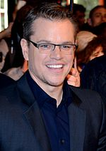 A man is wearing a navy blue collared shirt and glasses.