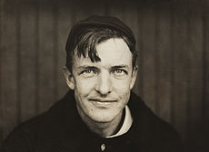 A dark-haired man wearing a black sweater and crownless baseball cap looks into the camera. His hair hangs down over his right side of his forehead, and he has a slight smirk on his face.