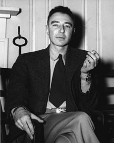 A man in a suit seated, smoking a cigarette.