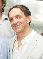 A man with light brown hair wearing a white coat and a white collared shirt.
