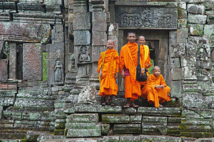 monks in orange robes on stone steps in Cambodia