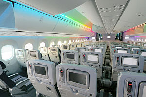 787 cabin. It shows the 787's spacious cabin. Above the blue seats are overhead bins and a rainbow light effect.