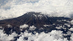 An aerial view of a large mountain's peak, encircled by many thick white clouds.