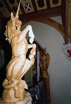 A photograph focusing on a large wooden sculpture of a unicorn, rearing on its hind legs. Behind it part of a wall and ceiling can be seen, the latter decorated with heraldic shields.