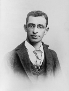 A 22-year-old man wearing an ill-fitting necktie, suit, and vest
