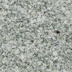 The polished face of a granite slab showing an even pattern of white, greenish and black crystals.