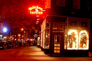 On the corner of a block is a building with large glass fronts on both sides; a sign displaying the tavern's name shines brightly above in red neon.