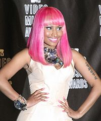 A tan-skinned woman in a bright pink wig poses with hands on both side of her hips. Smiling, she stands before a black background and has Mandarin characters tattooed on her right arm.