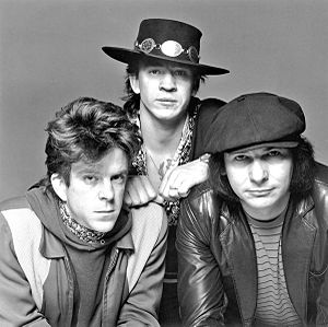 A black and white photograph of three men, one is wearing a wide-brimmed black hat.