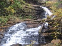 A slide of white water with a ninety degree turn at the halway point, with a stair step like character in the stone beneath. It is autumn and bright yellow leaves appear in the trees over the falls. Newly fallen leaves are visible on the rocks around the falls.