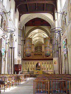 An interior view of the nave of Rochester Cathedral, looking towards the east. The nave has Norman arches and a flat wooden ceiling, beyond which there the stone vault of the choir. The cathedral is divided by a stone screen on which rest two section of richly decorated organ pipes.