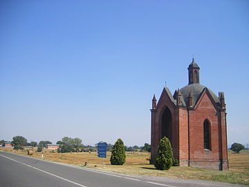 Photo of a small brick chapel on a highway amid rolling pastures. A sign reads Voghera to the right and Piacenza to the left.