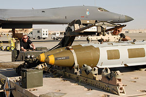 Ammunition and yellow bombs lay as two crew member, using lift truck, transfer them to a gray B-1 parked nearby in the background