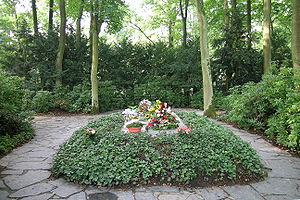 Several floral tributes are laid on a flat gravestone that is in the middle of a large bed full of low leafy plants. A crazy-paved path passes either side of the bed.