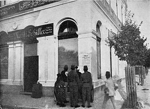"Photo of large white building with one signs saying ""Moritz Schiller"" and another in Arabic; in front is a cluster of people looking at poster on the wall."