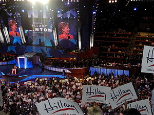 "Clinton speaking on behalf of Barack Obama before a convention audience during the second night of the 2008 Democratic National Convention in Denver. Multiple audience members in the foreground wave white flags with the word ""Hillary"" written in marker."
