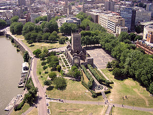 The walls and tower of an old ruined church set in a paved area and surrounded by a park. On the left is water with some pontoons moored and in the background office blocks, streets and church spires.